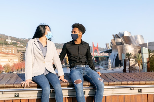 Portrait of a couple of young friends sitting in bilbao with a happy blue sky with face masks due to the 2020 covid-19 coronavirus pandemic