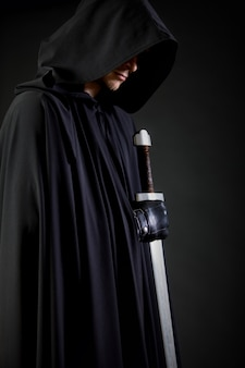 Portrait of a courageous warrior wanderer in a black cloak and sword in hand.