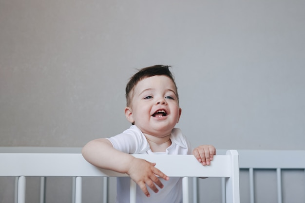 Portrait of a crawling and smilling boy baby in white bodysuit on the bed in bedroom. blue big eyes .happy childhood concept with copyspace side view
