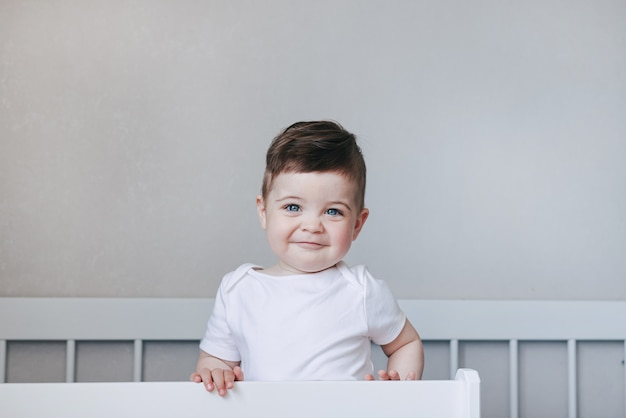 Portrait of a crawling and smilling boy baby in white bodysuit on the bed in bedroom. blue big eyes .happy childhood concept with copyspace