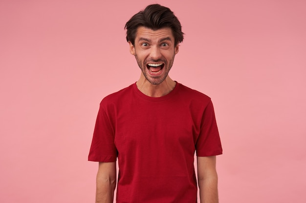 Portrait of crazy angry young man with bristle and opened mouth in red tshirt looks mad and screaming