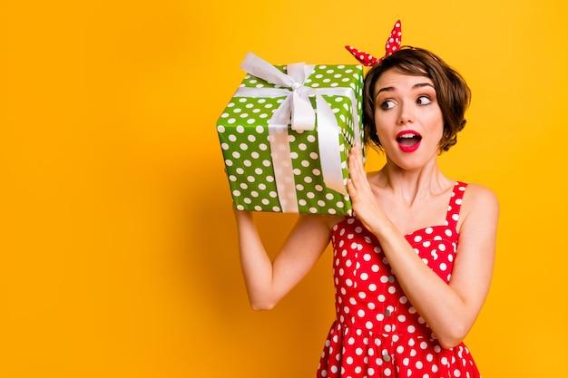 Портрет сумасшедшей удивленной девушки празднует 8 марта получить большую зеленую подарочную коробку впечатлен крик вау, омг, встряхнуть хочу знать, что она получает, носить юбку в стиле ретро, изолированную яркую цветную стену