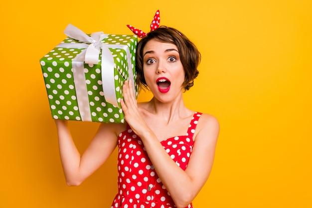 Портрет сумасшедшей удивленной девушки получить большую зеленую подарочную коробку мечты встряхнуть ее хочу знать, что парень подарит ей 14 февраля носить одежду в винтажном стиле, изолированную желтую стену