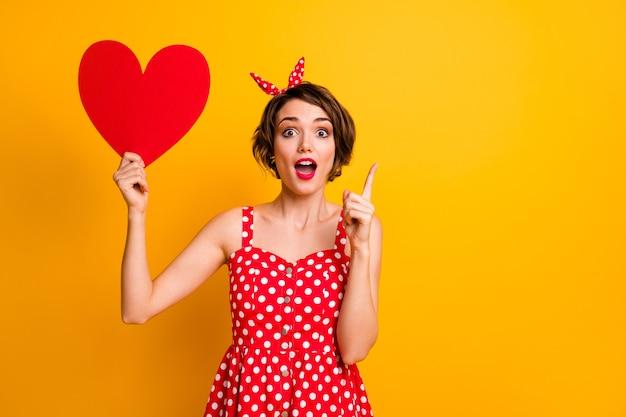 Портрет сумасшедшая изумленная девушка держит большую красную бумажную открытку сердце решает чувства парень получает прекрасную идею поднять указательный палец кричать носить винтажный стиль наряд изолированный блеск цвет стены