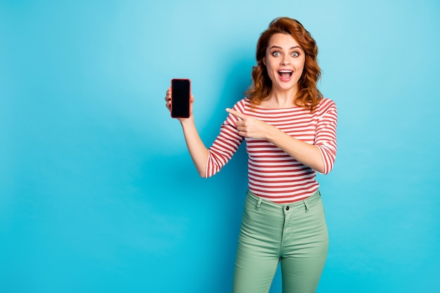 Portrait of crazy astonished girl hold new modern smartphone point index finger advise choose scream wow omg wear white sweater isolated over blue color