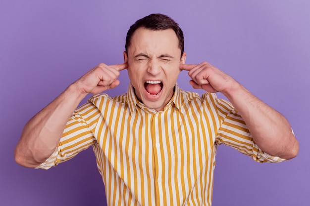 Portrait of crazy avoiding guy fingers cover ears shout close eyes on violet background