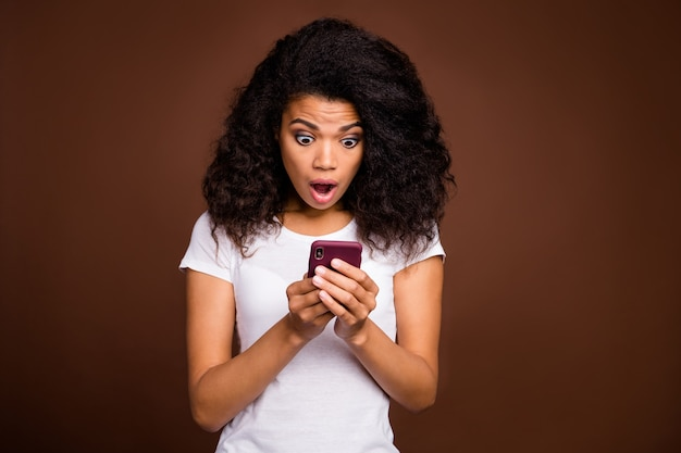Portrait of crazy funky afro american girl use smart phone read social network information impressed scream wow omg wear casual style clothing.