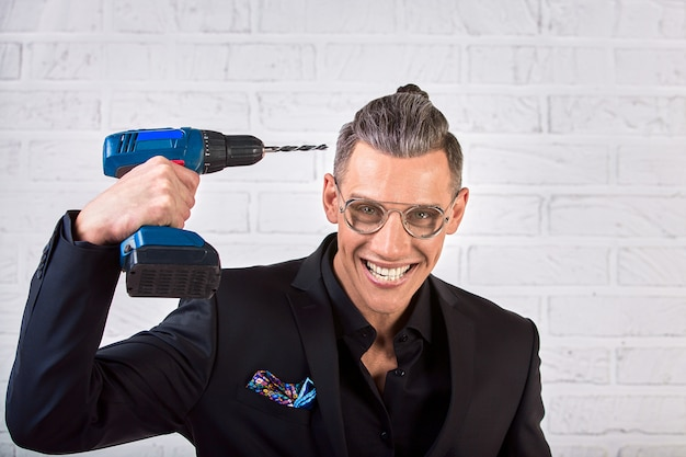 Portrait of crazy funny young man in black suit smiling with a drill holds at his temple. fuck the brain