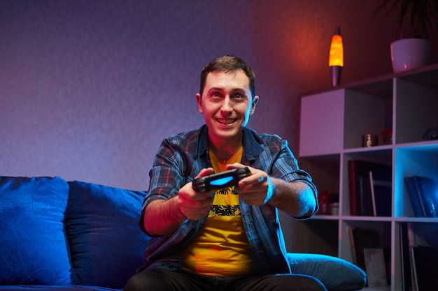 Portrait of crazy playful gamer, boy enjoying playing video games indoors sitting on the sofa, holding console gamepad in hands. resting at home, have a great weekend