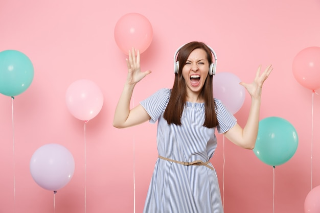 Portrait of crazy pretty young woman with headphones wearing blue dress listening music spreading hands screaming on pastel pink background with colorful air balloons. birthday holiday party concept.