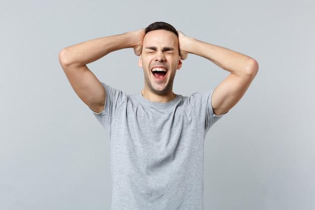 Ritratto di un giovane pazzo urlante in abiti casual che tiene gli occhi chiusi e mette le mani sulla testa