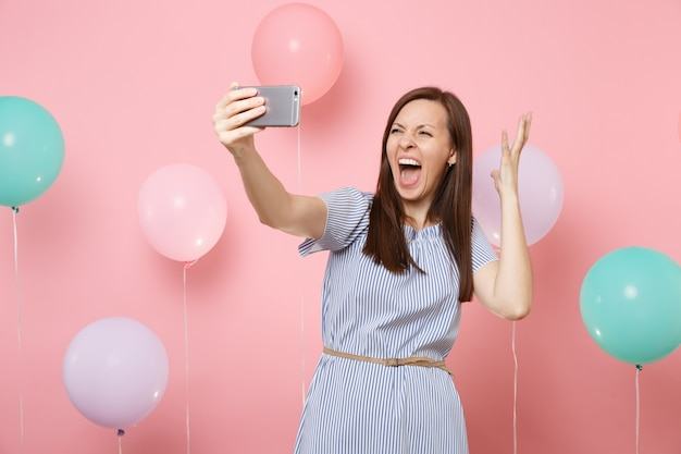 Portrait of crazy young woman in blue dress doing selfie on mobile phone screaming spreading hands on pastel pink background with colorful air balloons. birthday holiday party people sincere emotions.