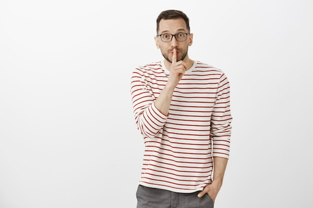 Portrait of creative good-looking adult male designer in striped shirt, asking keep secret, shushing and making shh gesture with index finger over mouth, being intrigued and happy over gray wall