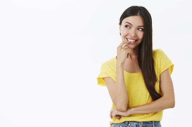 Ritratto di ragazza felice creativa e misteriosa con bei capelli scuri lunghi che tengono il dito sul labbro che sorride con gioia guardando a sinistra