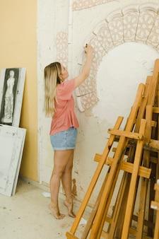 Ritratto della giovane donna creativa che scolpisce sulla parete con lo strumento