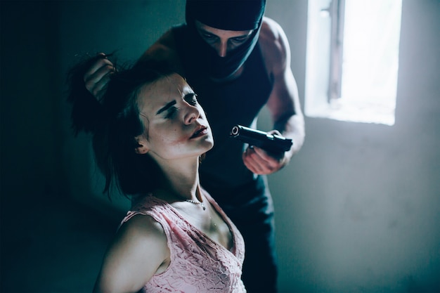 Portrait of cruel kidnapper holding girl's hair in hand and holding gun very close to his face. he wears mask. guy is looking at girl. she is keeping her eyes close. girl is afraid and terrified.