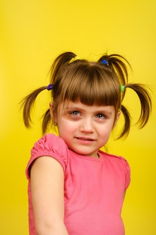 Portrait of crying little caucasian girl with pigtails and bruise under the eye