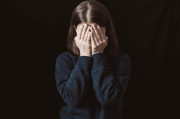 Portrait of a crying woman covering her face with hands . violence in family. sadness and depressive state of the girl.