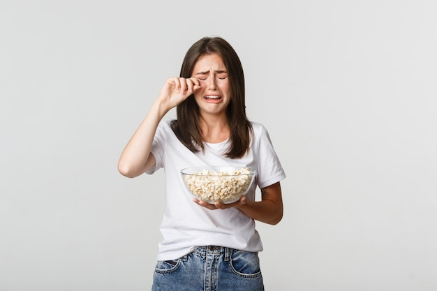 Portrait of crying young cute girl watching drama movie or tv series with bowl of popcorn.