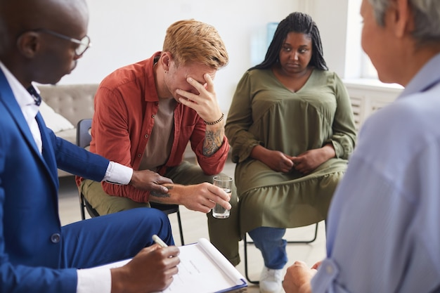 Portrait of crying young man sharing his troubles during support group meeting with people siting in circle and comforting him