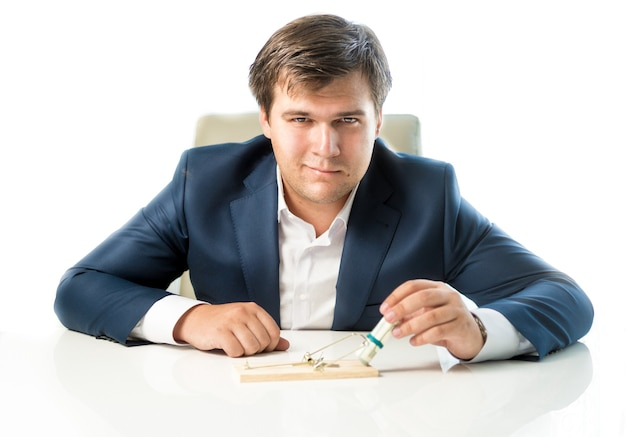 Portrait of cunning businessman putting money in trap as lure