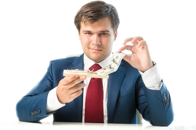 Portrait of cunning businessman taking dollar bill out of mousetrap
