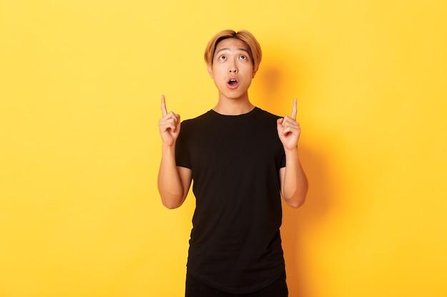 Ritratto di ragazzo asiatico curioso e stupito con i capelli biondi, indossa una maglietta nera, guardando e puntando il dito verso l'alto stupito, muro giallo