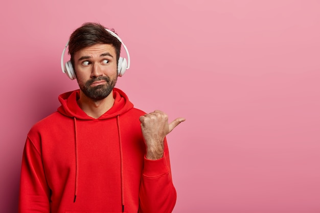 Portrait of curious bearded man points thumb away on blank space right, wears stereo headset and red casual sweatshirt, demonstrates something interesting, isolated on pink pastel wall.