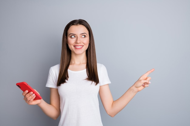 Portrait of curious cheerful girl using cell demonstrating copy space