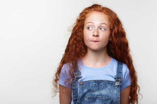 Ritratto di curioso carino lentiggini bambina con i capelli allo zenzero, pensando a qualcosa, morde le labbra, distoglie lo sguardo su sfondo bianco con copia spazio sul lato sinistro.