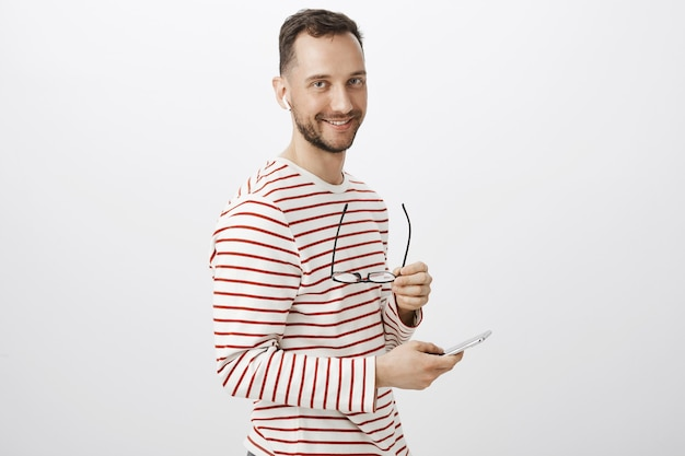 Portrait of curious handsome european gay in striped pullover, taking off glasses and waiting for boyfriend call in wireless earphones