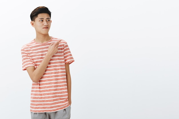 Portrait of curious nice young asian male model in striped t-shirt standing relaxed over grey wall with hand in pocket looking and pointing at upper right angle seeing interesting copy space