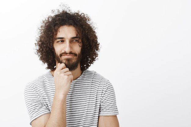 Portrait of curious playful handsome male with curly hair, looking aside and smirking, holding hand on beard while thinking and having great plan