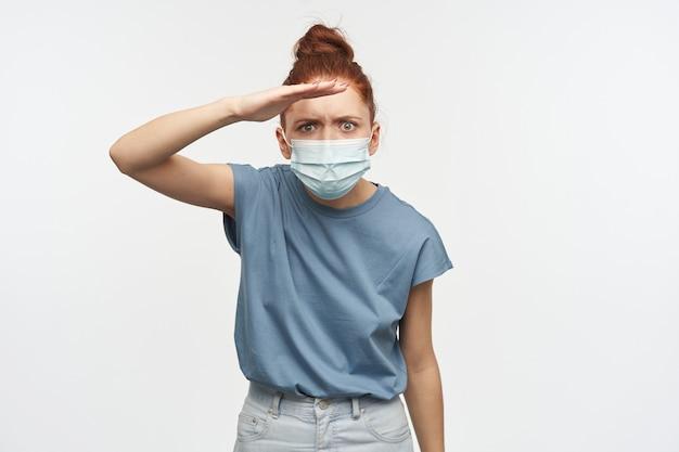 Ritratto di ragazza curiosa rossa con i capelli raccolti in un panino. indossare una maschera protettiva. tenendo la mano sopra gli occhi e scrutando in lontananza. isolato su muro bianco