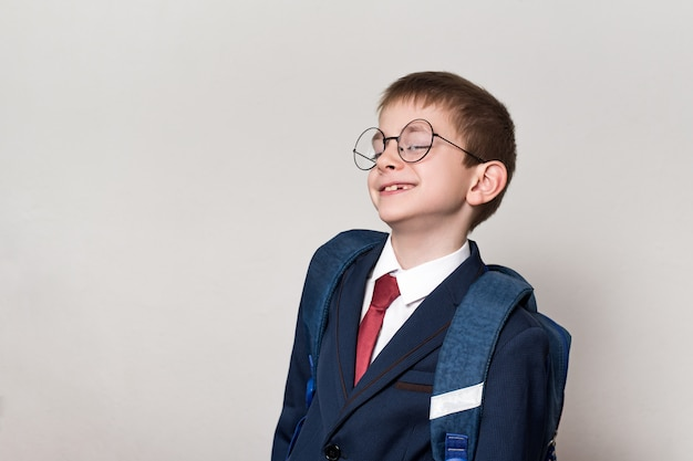 Portrait of a curious schoolboy in a suit, glasses and a backpack.