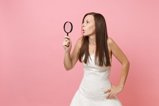 Portrait of curious shocked woman in white dress looking aside through magnifying glass
