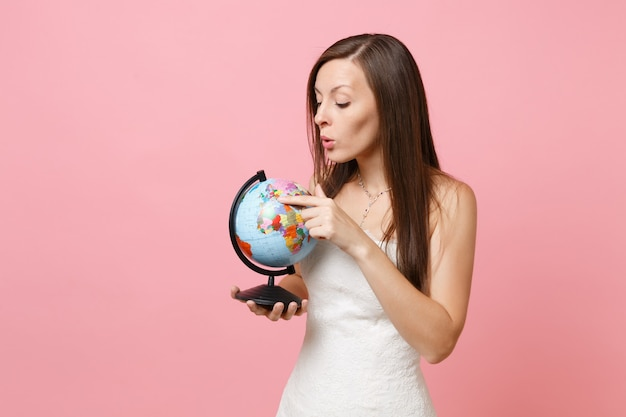 Portrait of curious woman in lace white dress pointing index finger on world globe, choosing place