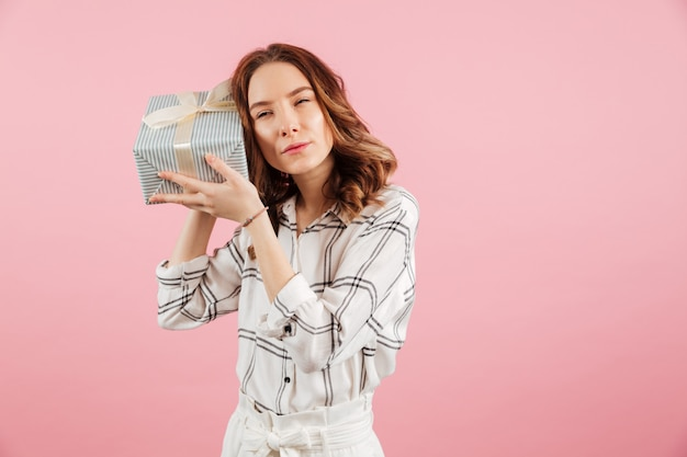 Portrait of a curious young woman holding a gift box