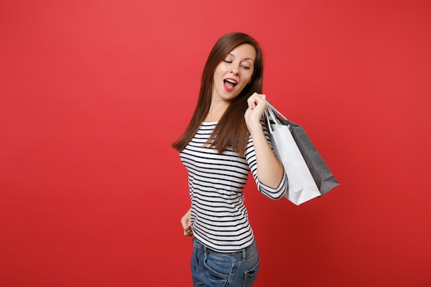 Portrait of curious young woman looking back on packages bags with purchases after shopping in hands isolated on red wall background. people sincere emotions, lifestyle concept. mock up copy space.