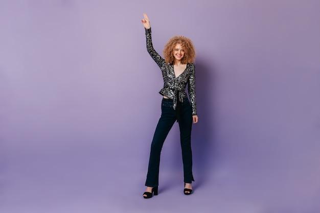 Ritratto di bionda riccia in abiti da discoteca. la signora in camicetta nera con perline d'argento sta ballando in uno spazio isolato.