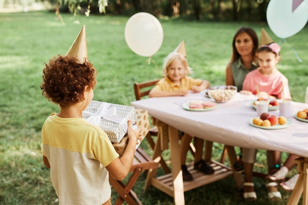 Portrait of curly boy carrying gifts during outdoor birthday party with friends in summer copy space