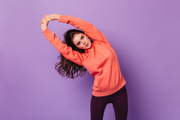 Portrait of curly brunette woman doing exercises on purple wall