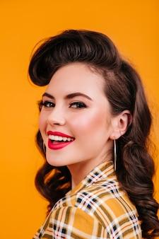 Ritratto di donna bruna riccia con un sorriso affascinante. studio shot di beata ragazza pinup che ride su sfondo giallo.