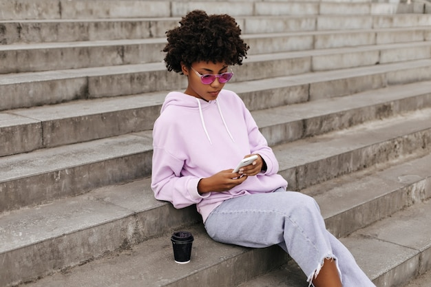 Portrait of curly cheerful girl in denim pants, pink sunglasses and purple hoodie holding phone and sitting on stairs outdoors