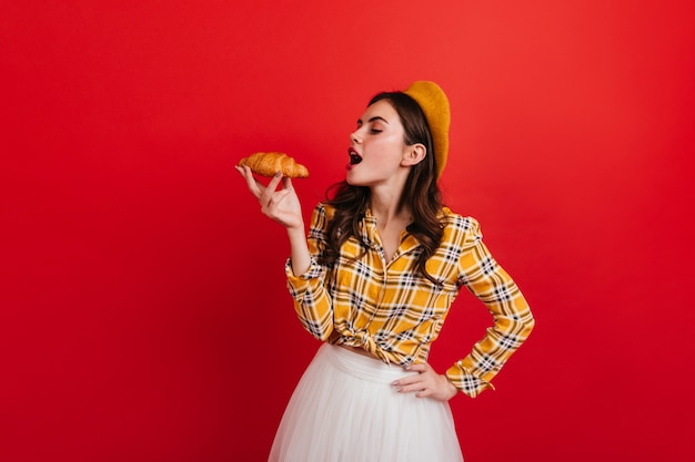 Portrait of curly french girl eating crispy croissant on red wall. dark-haired woman in checkered blouse and yellow hat looks at bun.