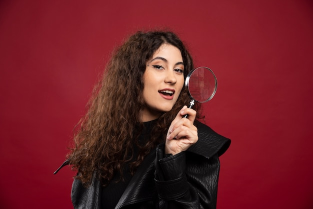 Portrait of curly girl holding magnifying glass.