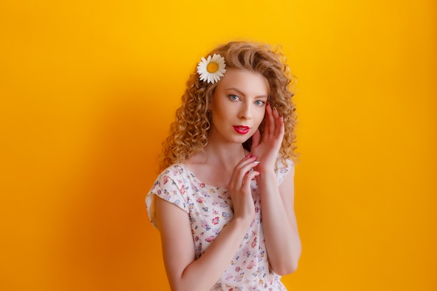 Portrait of a curly girl with a daisy in her hair on yellow