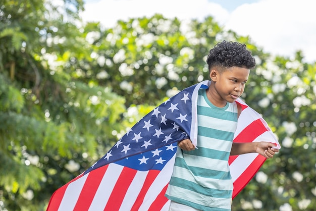 Portrait of curly hair boy american with his back draped and blanket with the american flag