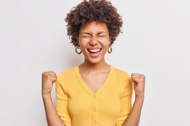 Portrait of curly haired woman clenches fists celebrates success feels happy after winning or triumph wears casual yellow jumper isolated over white wall
