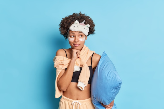 Portrait of curly haired woman keeps hand under chin looks pensively aside dressed in nightwear holds pillow going to have sleep isolated over blue wall